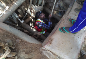 Geologist Gideon Lambiv emerging from mining shaft – 150 ft deep.